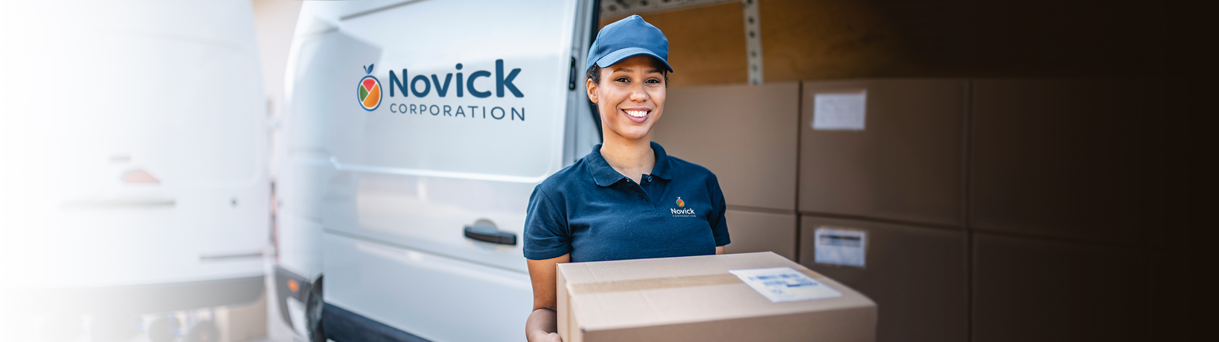 food distributors - Person standing in front of a Novick delivery truck holding a box - Novick Corporation - Pennsylvania