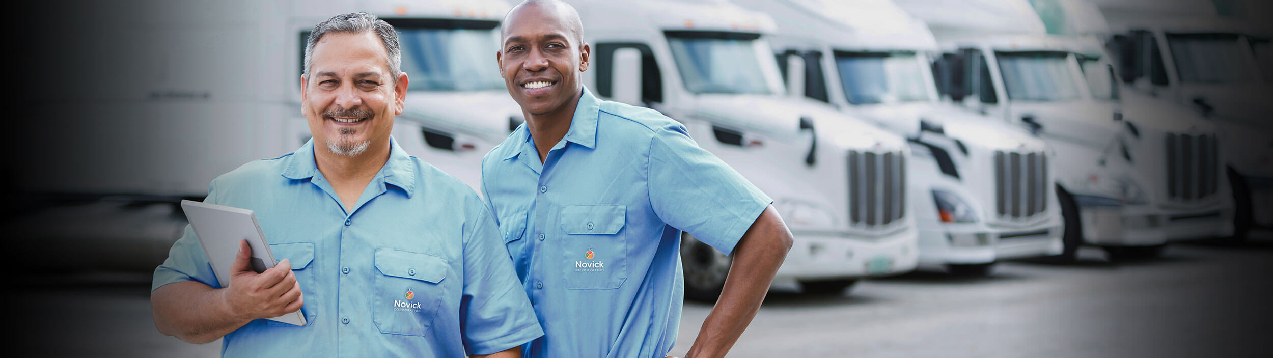 wholesale food distributors in PA - two people standing in front of Novick trucks - Novick Corporation
